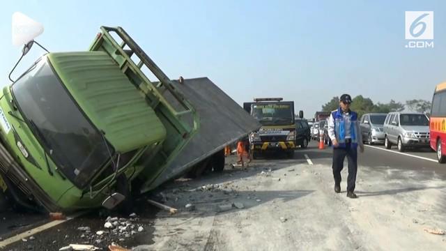 Truk pengangkut material beton oleng dan menabrak pembatas jalan tol, sementara minibus di belakangnya menabrak bagian belakamg truk.