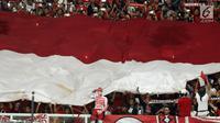 Suporter membentangkan bendera Merah Putih raksasajelang menyaksikan laga Timnas Indonesia U-19 melawan Jepang U-19 pada perempat final Piala AFC U-19 2018 di Stadion GBK, Jakarta, Minggu (28/10). Indonesia kalah 0-2. (Liputan6.com/Helmi Fithriansyah)