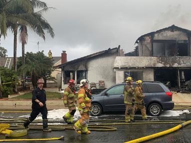 Petugas pemadam kebakaran usai memadamkan api di lokasi kecelakaan pesawat di sebuah rumah di Yorba Linda, California (3/2). Pesawat Cessna 414A jatuh di Yorba Linda tak lama setelah lepas landas dari Bandara Fullerton Municipal. (AP Photo/Alex Gallardo)