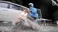 Pengendara sepeda motor menerobos banjir yang menggenangi Jalan DI Panjaitan, Jakarta, Senin (3/12). Banjir juga disebabkan adanya pengerjaan proyek Tol Becakayu yang berada di jalan tersebut. (Merdeka.com/ Iqbal S. Nugroho)