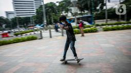 Aksi warga saat bermain skateboard di trotoar Jalan Sudirman-Thamrin, Jakarta, Jumat (5/3/2021). Gubernur DKI Jakarta Anies Baswedan mengizinkan trotoar untuk digunakan sebagai tempat bermain skateboard dengan beberapa kesepakatan. (Liputan6.com/Faizal Fanani)