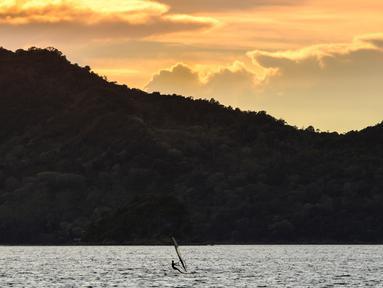 Seorang pria bermain selancar angin saat matahari terbenam di sebuah pantai di Banda Aceh (7/4). Kota Banda Aceh merupakan salah satu kota yang berada di Aceh dan menjadi ibukota Provinsi Aceh, Indonesia. (AFP Photo/Chaideer Mahyuddin)