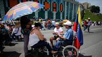 Demonstran anti-pemerintah memainkan kartu di jalan raya saat unjuk rasa melawan Presiden Nicolas Maduro, di Caracas, Venezuela, (15/5). Para demonstran menuntut Presiden Nicolas Maduro mundur dari jabatannya. (AP Photo / Ariana Cubillos)