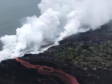 Lava pijar Gunung Kilauea saat mengalir ke laut di dua lokasi dekat Pahoa, Hawaii, Amerika Serikat, Senin (21/5). Lava pijar mengalir ke laut dan memicu reaksi kimia yang menciptakan awan raksasa asam dan kaca halus. (Survei Geologi AS via AP)