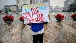 Buruh membentangkan poster saat menggelar unjuk rasa di Bundaran HI, Jakarta, Kamis (20/8/2015). Dalam aksinya mereka menuntut Panarub Dwikarya, buyer Adidas dan Mizuno menyelesaikan kasus PHK massal terhadap 1.300 pekerja. (Liputan6.com/Faizal Fanani)