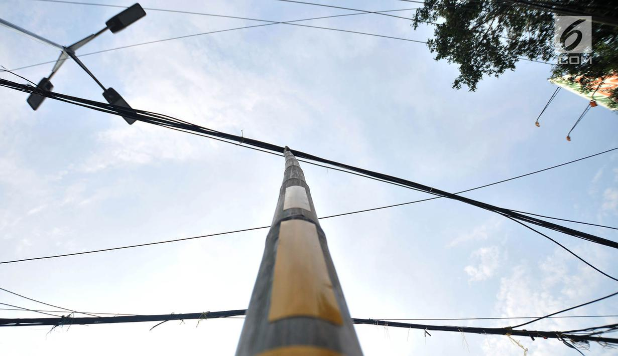 Bambu penyangga kabel terlihat di Jalan Wahid Hasyim, Jakarta, Selasa (6/11). Dua buah bambu penyangga kabel menjuntai yang sudah ada sejak beberapa hari lalu tersebut berada di tengah jalan. (Merdeka.com/Iqbal S. Nugroho)