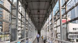 Pejalan kaki melintasi JPO Gelora Bung Karno di Jakarta, Kamis (3/5). Prioritas utama yang akan direnovasi terlebih dahulu, yaitu JPO Polda Metro Jaya, JPO Ratu Plaza, dan JPO Gelora Bung Karno. (Liputan6.com/Immanuel Antonius)