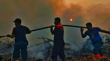 Pemadaman titik kebakaran hutan dan lahan atau karhutla oleh petugas.