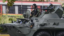 Sebuah tank lapis baja dari tentara Venezuela melewati jalan raya Caracas, Venezuela, Senin (15/1). Dua petugas polisi tewas dalam serangan Oscar Perez ke  kantor Mahkamah Agung (MA) Venezuela. (AFP PHOTO/JUAN BARRETO)