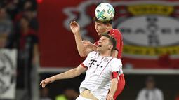 Penyerang Bayern Munchen, Thomas Mueller, duel udara dengan bek Bayer Leverkusen, Panagiotis Retsos, pada laga DFB Pokal di Stadion BayArena, Selasa (17/4/2018). Bayern Munchen menang 6-2 atas Bayer Leverkusen. (AP/Martin Meissner)