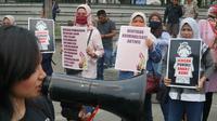 Sejumlah ibu-ibu di Bandung mengangkat poster-poster berisi protes kepada aparat atas dugaan represifitas saat mengamankan demonstrasi beberapa waktu lalu. (Liputan6.com/Huyogo Simbolon)