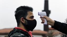Suhu tubuh warga diperiksa sebelum salat Jumat dengan menjaga jarak di depan sebuah masjid di Ankara, 29 Mei 2020. Masjid-masjid di seluruh Turki pada Jumat (29/5) kembali dibuka, sebagai bagian proses normalisasi di tengah melambatnya penyebaran COVID-19 di negara itu. (Xinhua/Mustafa Kaya)
