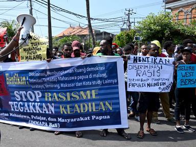 Ikatan Mahasiswa Pelajar dan Masyarakat Papua (IMMAPA) membawa spanduk saat berunjuk rasa di Lapangan Niti Mandala, Denpasar, Bali, Kamis (22/8/2019). Protes atas insiden yang terjadi di Asrama Papua di Surabaya ini diikuti oleh puluhan peserta. (SONNY TUMBELAKA/AFP)