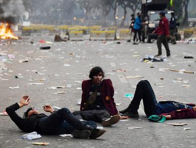 Sejumlah mahasiswa terkapar setelah polisi menembakkan gas air mata dalam demonstrasi menolak pengesahan RUU KUHP dan revisi UU KPK di depan Gedung DPR, Jakarta, Selasa (24/9/2019). Sejumlah mahasiswa tumbang setelah polisi menembakkan gas air mata untuk membubarkan demonstrasi. (ADEK BERRY/AFP)