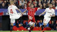 Aksi pemain Bayern, Javi Martinez (tengah) berusaha melewati adangan dua pemain Sevilla pada leg pertama Liga Champions di Sanchez Pizjuan stadium, Seville, (3/4/2018) waktu setempat. Beyern menang 2-1. (AP/Miguel Morenatti)
