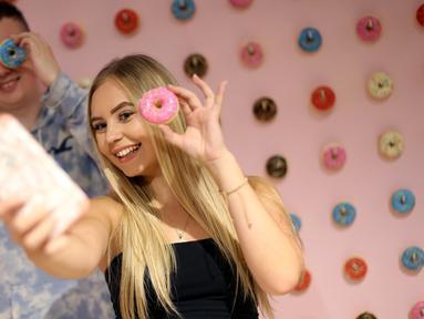 Pengunjung berswafoto ketika mengunjungi The Selfie Factory di pusat perbelanjaan Westfield, London pada 11 September 2019. Dengan membayar 10 poundsterling, pengunjung bisa berfoto di ruangan yang berlatar unik dan menggemaskan. (Isabel INFANTES / AFP)