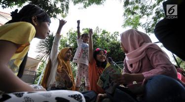 Antusiasme anak-anak mengikuti kuis saat program Literasi Kejujuran di TBM Saung Manggar, Jakarta, Minggu (24/3). Literasi Kejujuran merupakan program yang diinisiasi Suku Dinas Perpustakaan dan Kearsipan Jakarta Timur awal 2019 yang tersebar di taman-taman. (merdeka.com/Iqbal S. Nugroho)