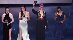 Penyerang Amerika Serikat, Megan Rapinoe (kedua kanan) mengangkat trofi pemain Wanita FIFA Terbaik 2019 saat berpose bersama Rose Lavelle, Alex Morgan dan Marta teater La Scala Milan, Italia utara (23/9/2019). (AFP Photo/Marco Bertorello)