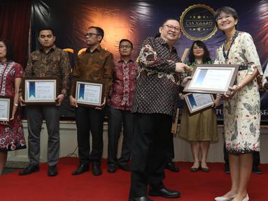 Ketua Umum PROPAMI (kiri) memberi piagam penghargan kepada Head of Protokol and Public Affairs Irnawati W Kahardja yang mewakili PT Surya Citra Media (SCM) Tbk dalam CSA Award 2019, Jakarta, Kamis (18/7/2019). SCM mendapat penghargaan CSA Award 2019 katagori growth stock. (Liputan6.com/Angga Yuniar)