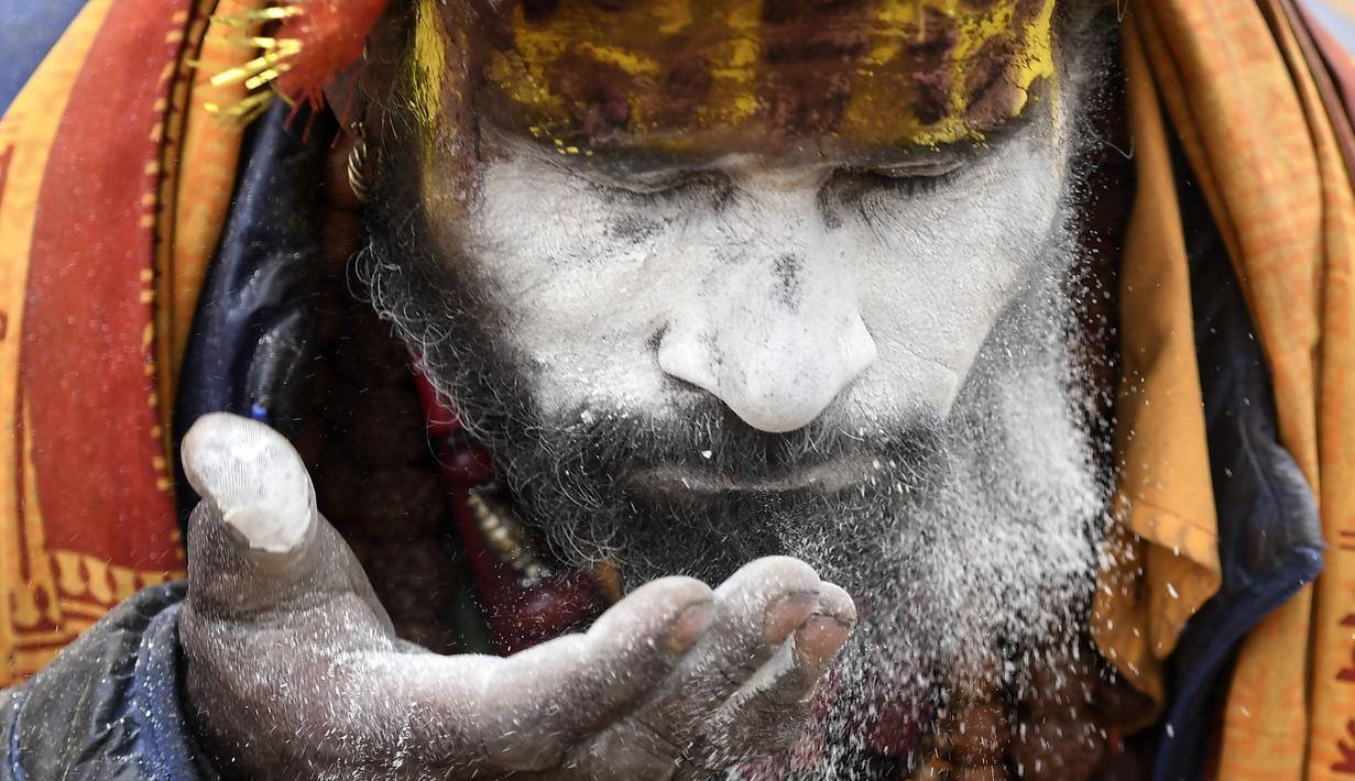 Seorang Sadhu (orang suci Hindu) mengoleskan wajahnya di dekat kuil Pashupatinath pada malam festival Hindu Maha Shivaratri di Kuil Pashupatinath di Kathmandu (20/2/2020). Maha Shivaratri, sebuah festival Hindu yang dirayakan sebelum kedatangan musim semi. (AFP/Prakash Mathema)