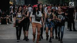 Sejumlah wanita berjalan untuk menyaksikan Konser Guns N' Roses di Stadion Gelora Bung Karno, Jakarta, Kamis (8/11). Di konser ini Guns N' Roses juga akan meng-cover sejumlah lagu dari para penyanyi populer. (Liputan6.com/Faizal Fanani)