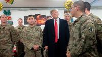 Presiden Donald Trump menyapa pasukan militer Amerika dalam kunjungan kejutan ke Pangkalan Udara al Asad, Irak, Rabu (26/12). Kunjungan ini merupakan kunjungan perdananya setelah mengumumkan penarikan pasukan militer dari Suriah. (SAUL LOEB/AFP)