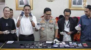 Kabid Humas Polda Metro Jaya Kombes Pol Argo Yuwono menunjukkan barang bukti kasus order fiktif pada transportasi online di Polda Metro Jaya, Jakarta, Rabu (13/2). Kasus ini diungkap oleh Satgas Cyber Crime Polda Metro Jaya. (Liputan6.com/Faizal Fanani)