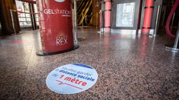 Penanda jaga jarak sosial dipasang di lantai Le Grand Rex sebelum bioskop itu dibuka kembali di Paris, Prancis (22/6/2020). Bioskop dan kasino kini kembali melanjutkan operasi dan kegiatan olahraga yang menarik tidak lebih dari 5.000 orang akan kembali diizinkan. (Xinhua/Aurelien Morissard)