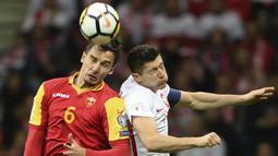 Striker Polandia, Robert Lewandowski, duel udara dengan bek Montenegro, Zarko Tomasevic, pada laga Kualifikasi Piala Dunia 2018 di Stadion National, Warsawa Minggu (8/10/2017). Polandia menang 4-2 atas  Montenegro. (AP/Alik Keplicz)