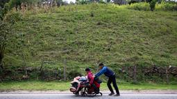 Migran Venezuela, Jefferson Alexis mendorong kursi roda ayahnya, Jose Agustin Lopez di Norte de Santander Department, Kolombia, 15 September 2018. Mereka harus menempuh 600 km dari Venezuela ke Bogota untuk mendapatkan pengobatan. (AFP/SCHNEYDER MENDOZA)