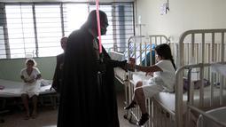 Seorang cosplayer berpakaian Darth Vader berbincang dengan seorang pasien saat acara amal oleh El Salvador Star Wars fan club di Rumah Sakit Benjamin Bloom Anak Nasional di San Salvador, El Salvador (14/12). (REUTERS/Jose Cabezas)