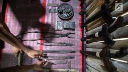 Empu Afrizal Fadli Azizi memegang keris Gagrag Banyumasan di Besalen Kyai Sela Pamujan Karangklesem, Banyumas, Jawa Tengah, Senin (22/4). Baselan atau bengkel keris mampu memproduksi tiga jenis keris Ageman, Tayuhan dan Cinderamata dengan lama pengerjaan 1 bulan-1 tahun. (Liputan6.com/Fery Pradolo)