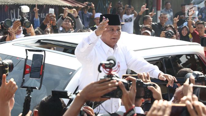 Calon Presiden no urut 02, Prabowo Subianto menyapa pendukungnya usai menggunakan hak pilihnya pada Pemilu 2019 di TPS 041 Kampung Curug, Desa Bojong Koneng, Babakan Madang, Kabupaten Bogor, Jawa Barat, Rabu (17/4). Prabowo didampingi Fadli Zon. (Liputan6