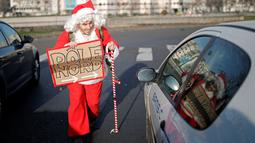 Remi Le Calvez, menghampiri sebuah mobil saat ia mencari tumpangan dengan mengenakan kostum Santa Claus di Paris, Prancis, Selasa (6/12). Remi membagi pengalaman dari perjalanannya kepada orang-orang lewat blog dan Facebooknya. (Reuters/Benoit Tessier)