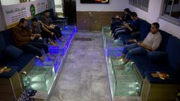 Warga Palestina merendam kaki mereka dalam akuarium berisi ikan di sebuah kafe di Kota Gaza, Palestina, Rabu (26/12/2018). Pedikur ikan tersebut dibanderol dengan harga 30 syikal atau sekitar 8 dolar AS per 30 menit. (AP Photo/Khalil Hamra)