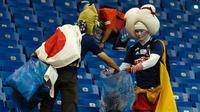 Suporter timnas Jepang mengumpulkan sampah setelah laga 16 besar Piala Dunia 2018 melawan Begia di Rostov Arena, Senin (2/7). Meski timnya tersingkir secara dramatis, tak menghalangi para suporter Jepang melakukan aksi positif. (AFP/JUAN BARRETO)