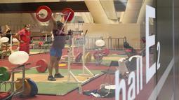 Seorang atlet Angkat Besi saat melakukan sesi latihan jelang Olimpiade di Tokyo, Selasa (20/7/2021). Pesta olahraga terbesar di dunia Olimpiade akan digelar pada 23 Juli 2021 hingga 8 Agustus 2021. (Foto: AP/Petr David Josek)