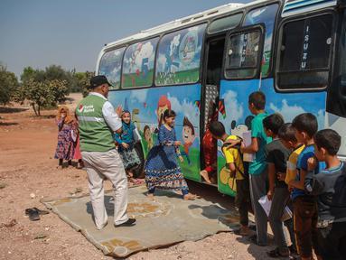 Anak-anak Suriah yang terlantar mengantre menaiki bus yang dikonversi menjadi ruang kelas di desa Hazano di barat laut Suriah (15/9/2019). Kelas di dalam bus ini hanya melayani usia mulai dari 5 hingga 12 tahun. (AFP Photo/Aaref Watad)