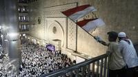 Peserta aksi mengibarkan bendera merah putih di Masjid Istiqlal, Jakarta, Sabtu (11/2). Massa yang kebanyakan mengenakan baju putih-putih ini datang dengan menggunakan kendaraan pribadi dan angkutan umum. (Liputan6.com/Herman Zakharia)