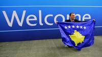 Seorang delegasi sepak bola Kosovo berfoto dekat tulisan selamat datang  saat merayakan diterimnya Kosovo sebagai anggota UEFA pada kongres UEFA ke-40 tahun di Hungexpo Fair Center, Budapest, Hungary, (3/52016). (AFP/Attila Kisbenedek)