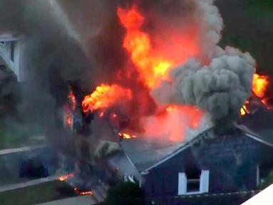 Gambar dari rekaman video memperlihatkan kobaran api membakar rumah di Lawrance, dekat Boston, Amerika Serikat (AS), Kamis (13/9). Rentetan ledakan dan kebakaran yang melanda tiga komunitas di utara Boston itu memaksa seluruh warga mengungsi (WCVB via AP)