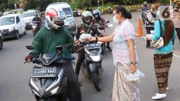 Sejumlah perempuan dengan mengenakan kebaya membagikan takjil untuk berbuka puasa bagi pengendara yang melintas di kawasan Tangerang, Banten, Rabu (21/4/2021). Pembagian takjil dengan mengenakan kebaya tersebut untuk merayakan Hari Kartini. (Liputan6.com/Angga Yuniar)