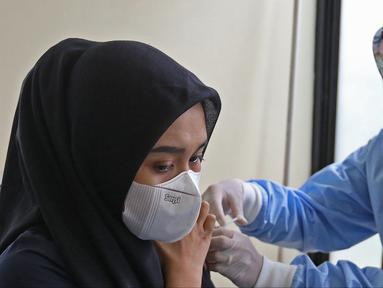 Petugas medis menyuntikan vaksin COVID-19  ke Seorang guru  di Puskesmas Jatiasih, Bekasi, Jawa Barat, Jumat (9/4/2021). Kementerian Pendidikan dan Kebudayaan menargetkan sebanyak 5,5 juta guru dan tenaga pendidik mengikuti vaksinasi COVID-19 sampai akhir Juni 2021. (Liputan6.com/Herman Zakharia)