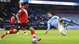 Pemain Southampton Ryan Bertrand (kiri) menendang bola di depan pemain Manchester City Bernardo Silva pada pertandingan Liga Inggris di Etihad Stadium, Manchester, Inggris, Rabu (10/3/2021). Manchester City menang 5-2. (Clive Brunskill/Pool via AP)