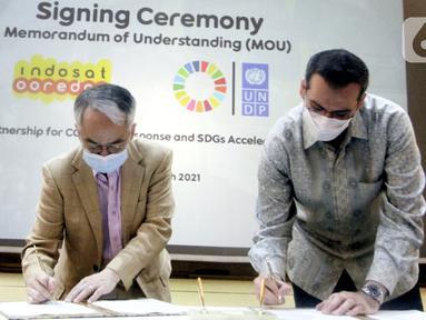 Resident Representative UNDP Indonesia, Norimasa Shimomura (kiri) dan Presdir & CEO Indosat Ooredoo, Ahmad Al-Neama (kanan) menandatangani MoU penanggulangan pandemi COVID-19 dan percepatan pencapaian Tujuan Pembangunan Berkelanjutan (SDGs) di Jakarta, Rabu (31/3/2021). (Liputan6.com/Pool/Indosat)