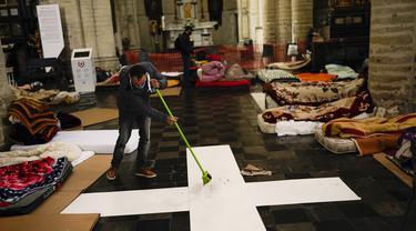 Seorang pria menyapu lantai saat dia bersama yang lainnya menempati gereja Saint-Jean-Baptiste-au-Beguinage di Brussels, Belgia, Selasa (2/2/2021). Beberapa ratus imigran tanpa surat-surat resmi, dengan izin pastor, telah menduduki gereja sejak Minggu, 31 Januari 2021 lalu. (AP Photo/Francisco Seco)