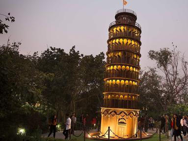 Pengunjung mengamati replika Menara Pisa di sebuah taman umum di New Delhi, 4 Februari 2020. Barang-barang bekas seperti besi batangan, suku cadang mobil, dan pipa dimanfaatkan untuk membuat tujuh keajaiban dunia yang ikonis di taman umum itu yang sukses menarik banyak pengunjung. (Xinhua/Javed Dar)