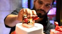 Pembuat kue memberikan sentuhan akhir pada sebuah kue berbentuk hati pada momen Hari Valentine di Damaskus, Suriah, Rabu (12/2/2020). (Xinhua/Ammar Safarjalani)