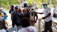 Petugas Kesehatan di perlintasan jalur antar kabupaten di Tolikara saat melakukan screening kepada warga yang melintas. (Liputan6.com/Katharina Janur/Satgas Covid-19 Tolikara)