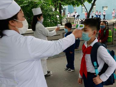 Siswa sekolah dasar Kim Song Ju diperiksa suhu tubuhnya sebelum memasuki sekolah di Pyongyang, Korea Utara, Rabu (3/6/2020). Korea Utara membuka kembali sekolah - sekolah di negara itu pada bulan ini setelah sebelumnya meliburkan karena kekhawatiran penyebaran virus corona. (AP/Jon Chol Jin)